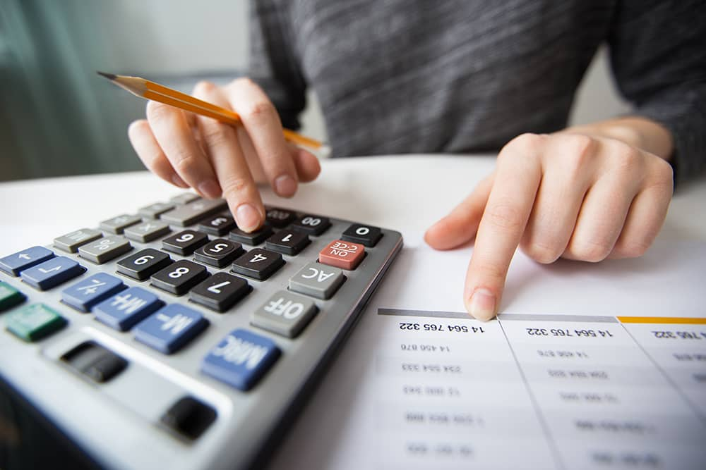 closeup-accountant-hands-counting-calculator